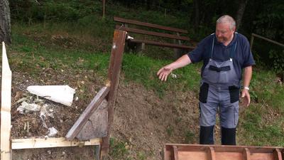 Imker steht vor einem Wildbienenhotel im Wald in Bad Herrenalb
