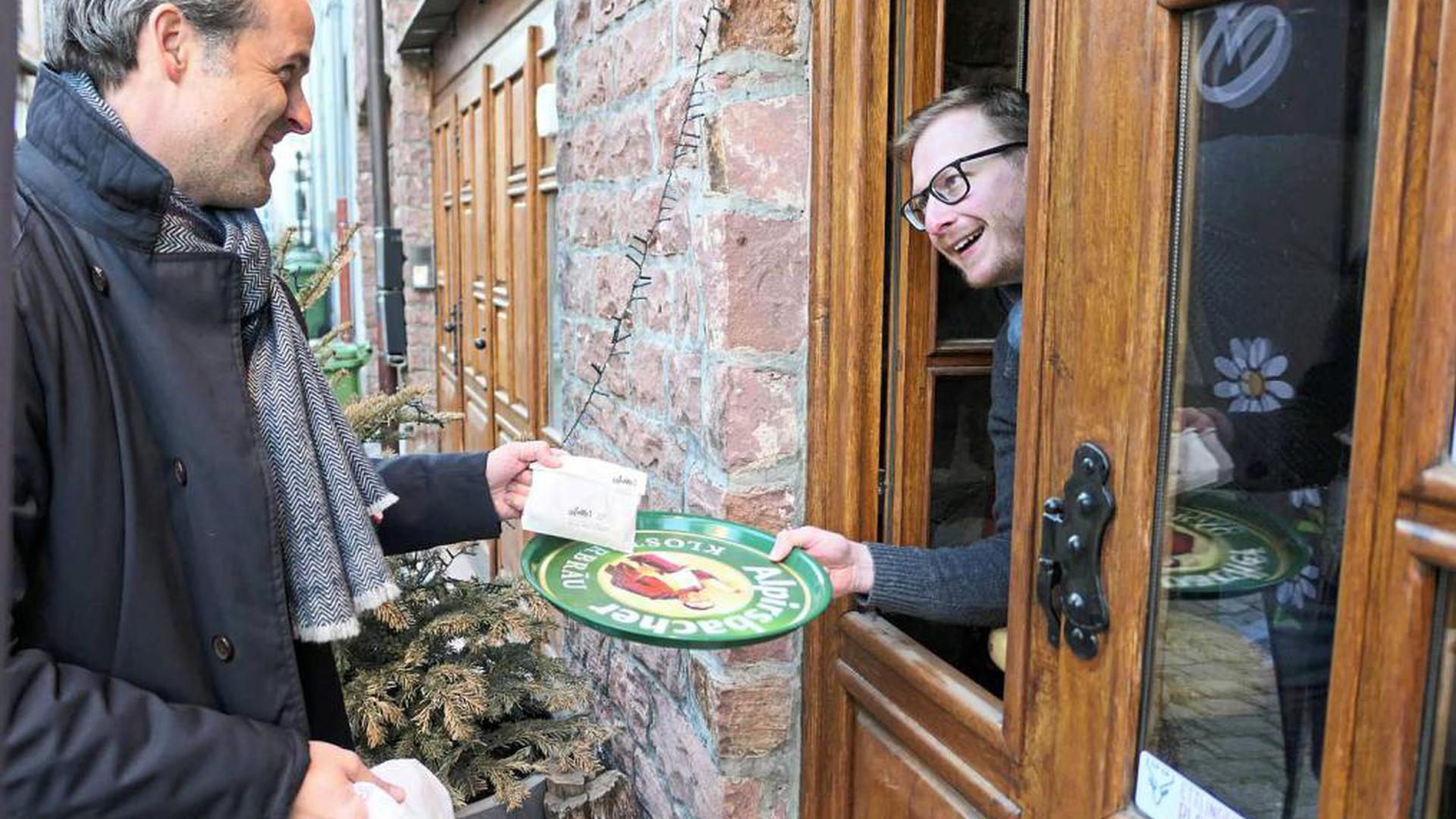 Patrick Seitz (links) von der Firma Aluplast nimmt seine bestellte Stulle entgegen in AnMa's Brasserie in Ettlingen entgegen.