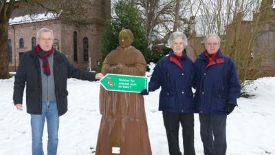 Drei Menschen stehen an einem steinernden Mönch