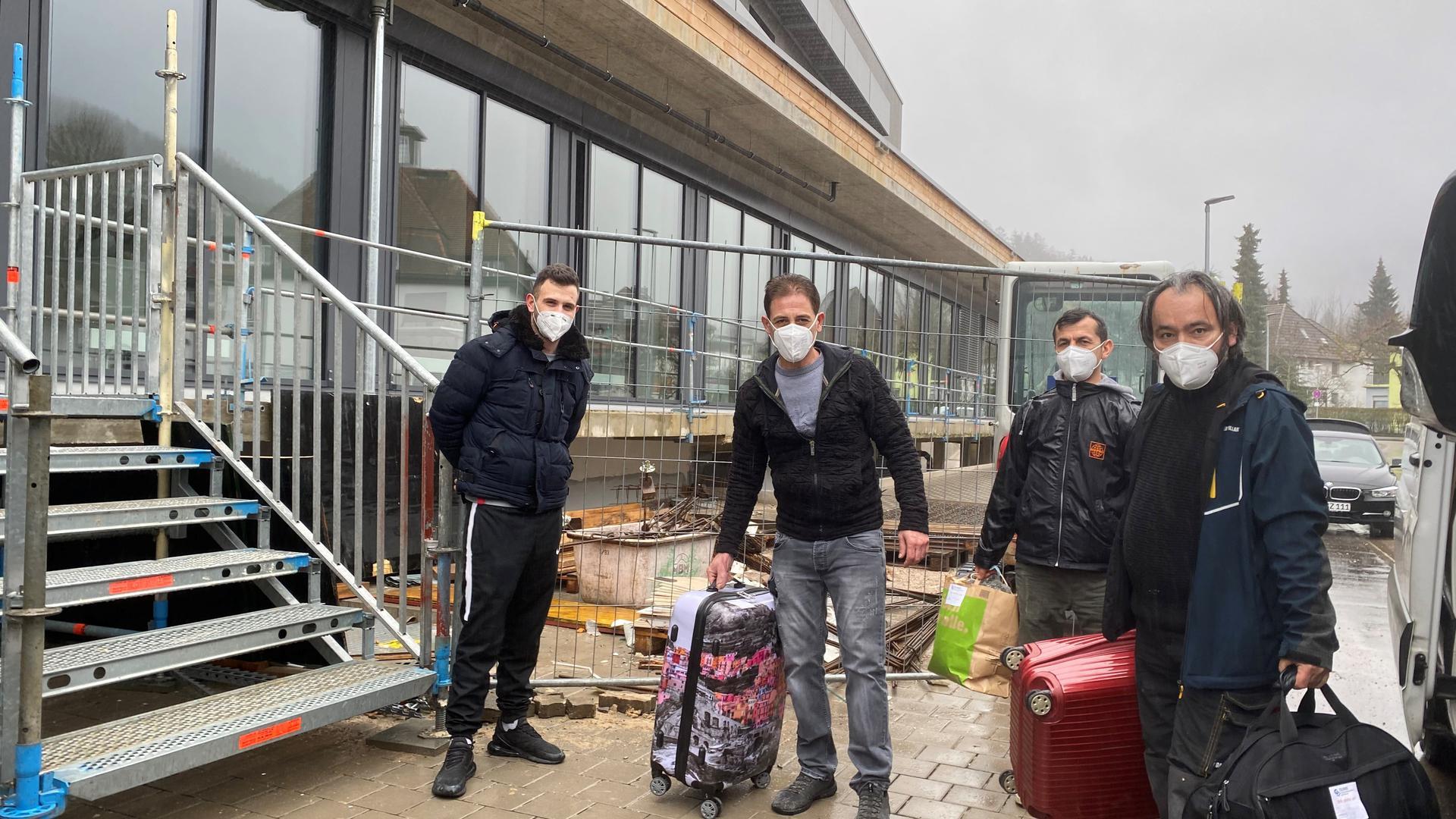 Männer mit Mund-Nase-Schutz und Koffern an Treppenaufgang