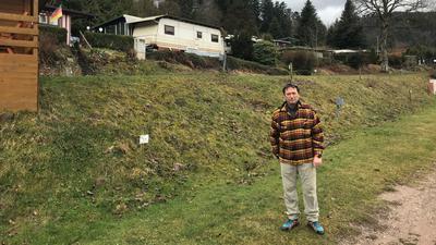 Mann. Im Hintergrund stehen Wohnwagen und ein Ferienhaus