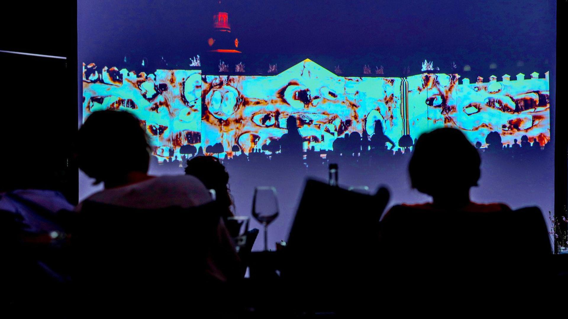 Menschen mit Glas vor einer Leinwand mit animierten Filmen