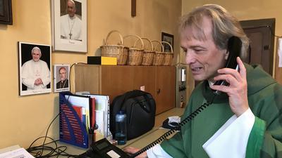Pfarrer Matthias Weingärtner in der Sakristei der katholischen Kirche St. Bernhard in Bad Herrenalb. Er begrüßt und verabschiedet persönlich die Teilnehmer des Telefongottesdienstes.