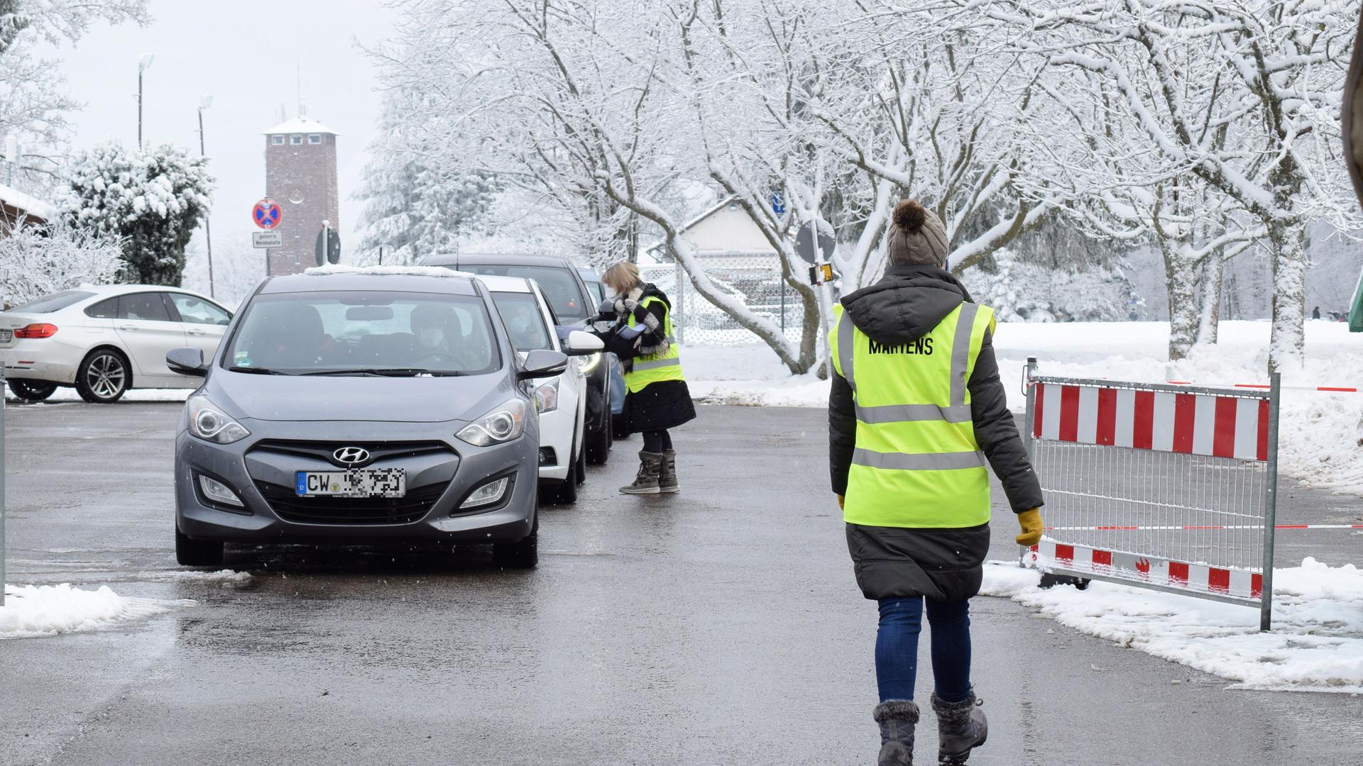 Zwei Security-Mitarbeiterinnen verteilen Merkblätter zum Coronavirus an die Testwilligen in Dobel