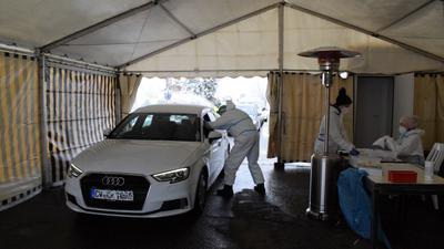 Arzt Hendrik Niehoff nimmt durch das geöffnete Autofenster einen Rachenabstrich bei einem Besucher des Corona-Testzentrums in Dobel.