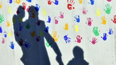ARCHIV - 08.04.2015, Bayern, München: Ein Mann mit einem Kind auf dem Arm und einem an der Hand wirft einen Schatten auf eine mit bunten Handabdrücken bemalte Wand einer Kindertagesstätte. Das Statistische Bundesamt veröffentlicht Zahlen zum Elterngeld (Leistungsbezüge 2019) mit Länderzahlen. Foto: Peter Kneffel/dpa +++ dpa-Bildfunk +++ | Verwendung weltweit