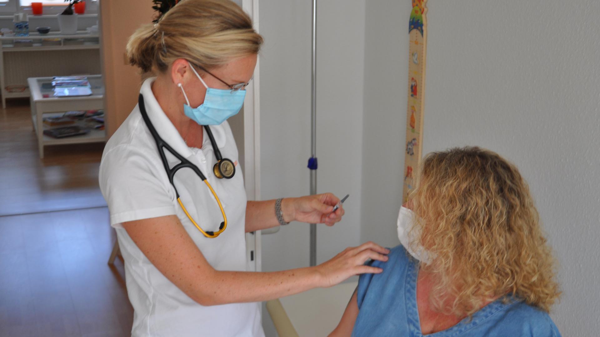 Ärztin mit Spritze und Patientin