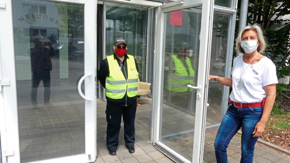 Unterkunftsleiterin Gabriele Germer (rechts) und der Mitarbeiter eines privaten Sicherheitsdienstes stehen am Eingang zur Quarantäne-Station.