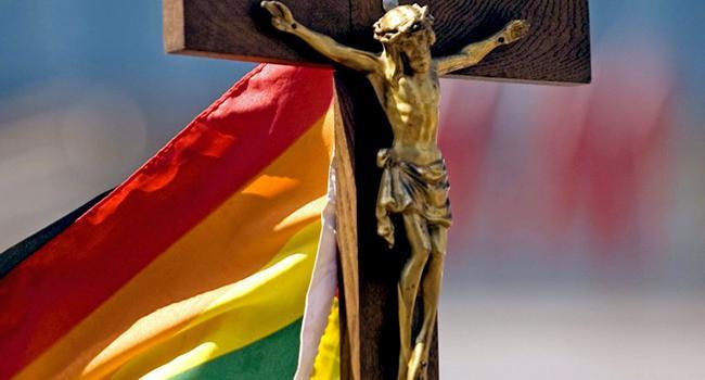 Jesus am Kreuz mit Regenbogenfahne im Hintergrund