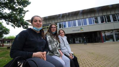 Die Realschülerinnen Lina, Paula und Aliya (von links) sitzen auf einer Bank auf dem Schulhof der Realschule in Karlsbad-Langensteinbach.