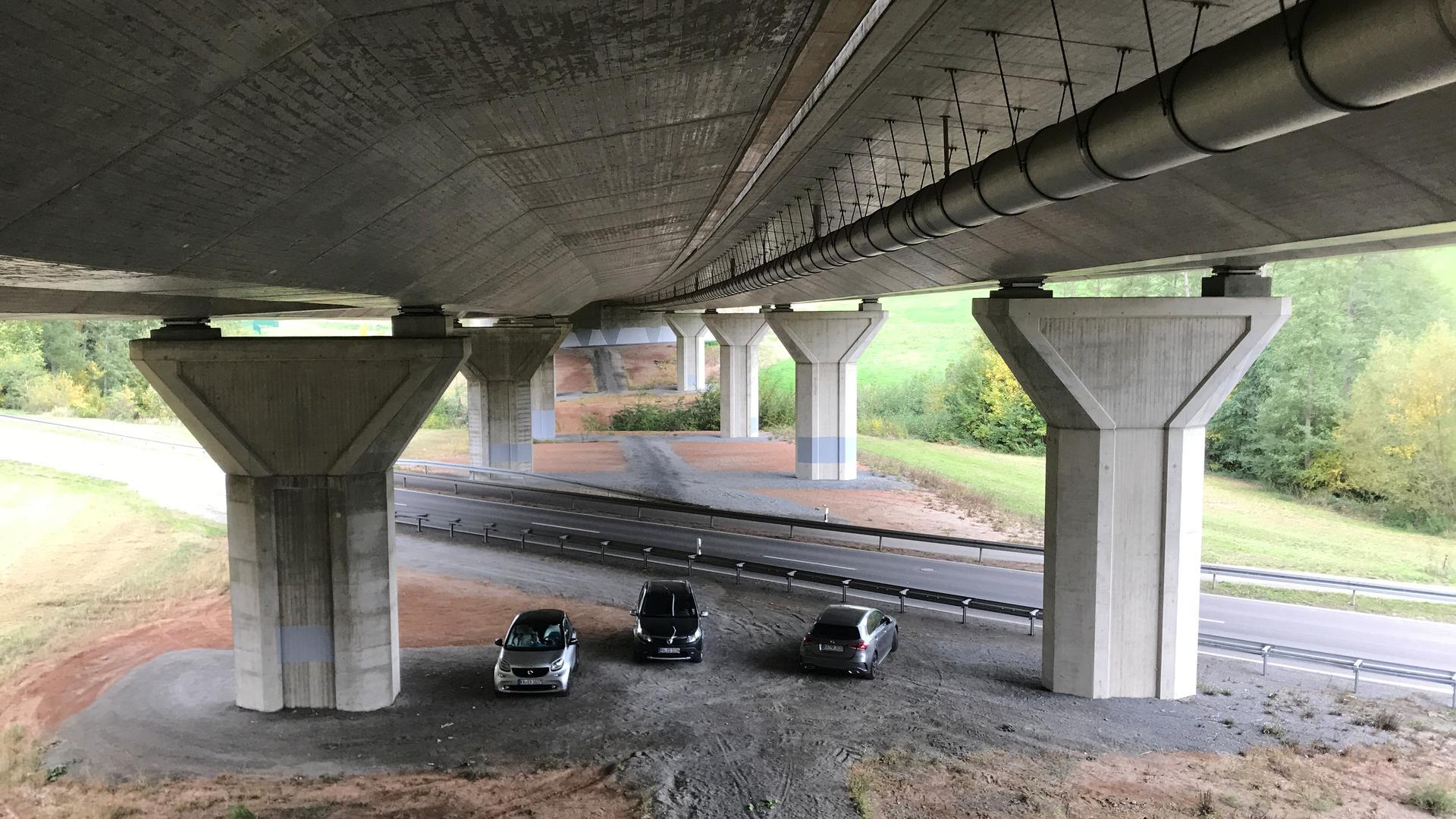 Pfeiler, drei Autos und Brückenbauerk von unten