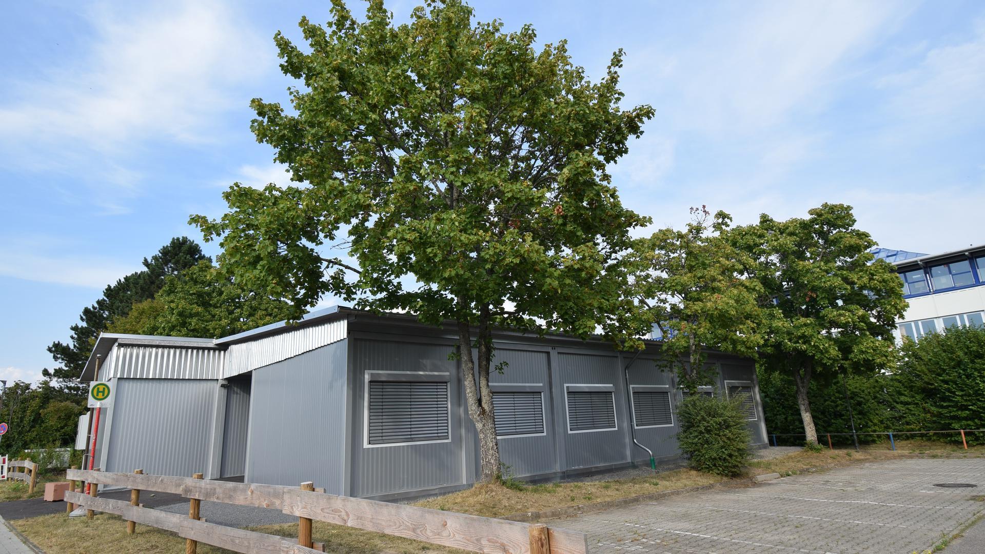 Blick auf mehrere, zusammenhängende Container auf einem Schulhof.