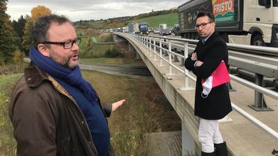 Zwei Männer, Brückengeländer und Lkw