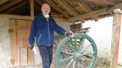 Gerne zeigt David Keppler in Mutschelbach historische landwirtschaftliche Gerätschaften. Die Achse mit den Holzrädern wurde als Sitzbank umgestaltet. Die Radnarben dieser Räder wurden vor rund 300 Jahren mit Schmiere der Obermutschelbacher Schmierbrenner eingerieben.