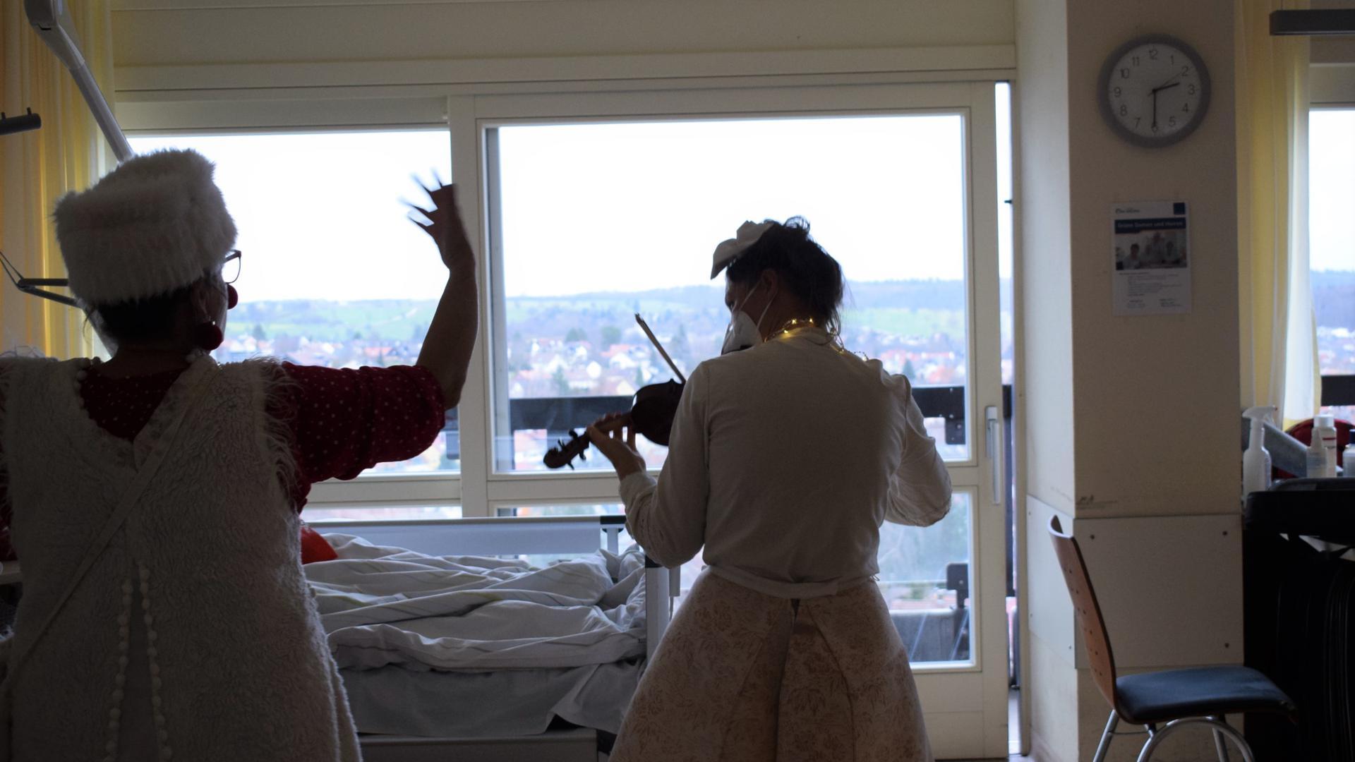 Der Clown spielt Geige: Berenike Felger (rechts) stimmt am Patientenbett ein Weihnachtslied an, Kollegin Doris Batzler dirigiert.