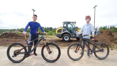 Maxim Ostrowski und Philip Sagawe stehen mit ihren Fahrrädern vor dem Gelände am Karlsbader Schulzentrum, auf dem der neuen Pumptrack entstehen soll. Im Hintergrund verteilen Bagger die Erde für den neuen Parcours.