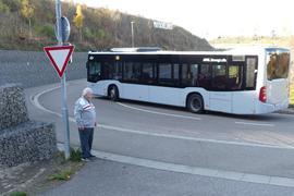 Ein Linienbus fährt durch die Spitzkehre hoch zur Omega-Brücke. Links steht Erwin Balzer.