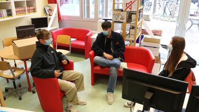 Jugendliche mit Maske auf Sofa und Sessel