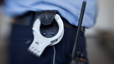 Handschellen hängen am Gürtel eines Justizbeamten.
