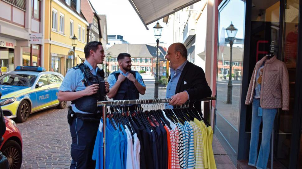 Verständnis zeigen Geschäftsinhaber, wie hier beim Herrenmodegeschäft Durm in Ettlingen, für die Beamten, die die Nachricht von der Schließung überbringen.