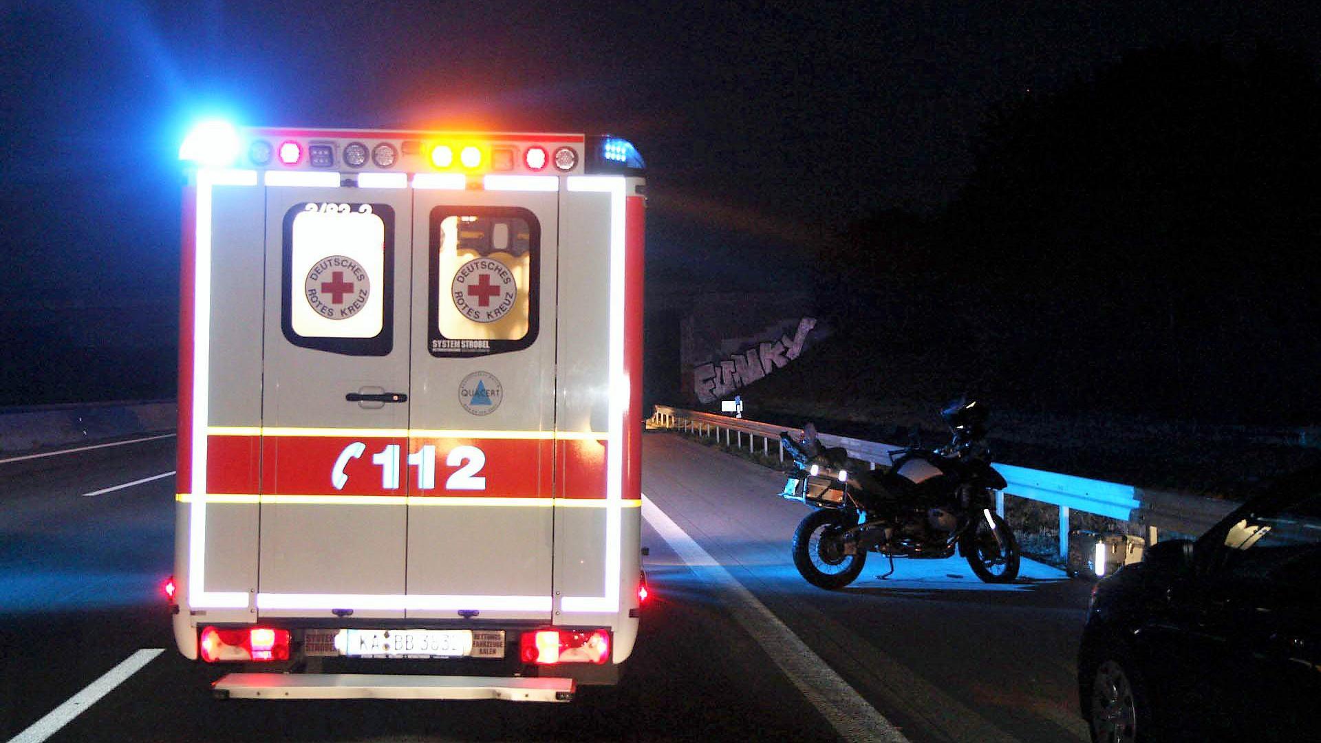 Ein Rettungswagen auf der Autobahn, daneben steht ein Motorrad.
