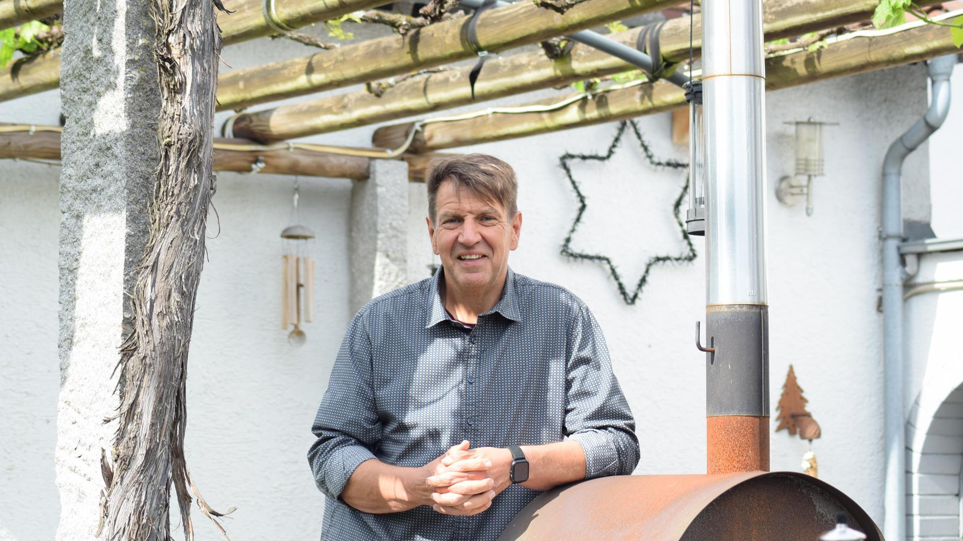 Bürgermeisterkandidat Markus Bechler steht im Garten seines Wohnhauses in Malsch.