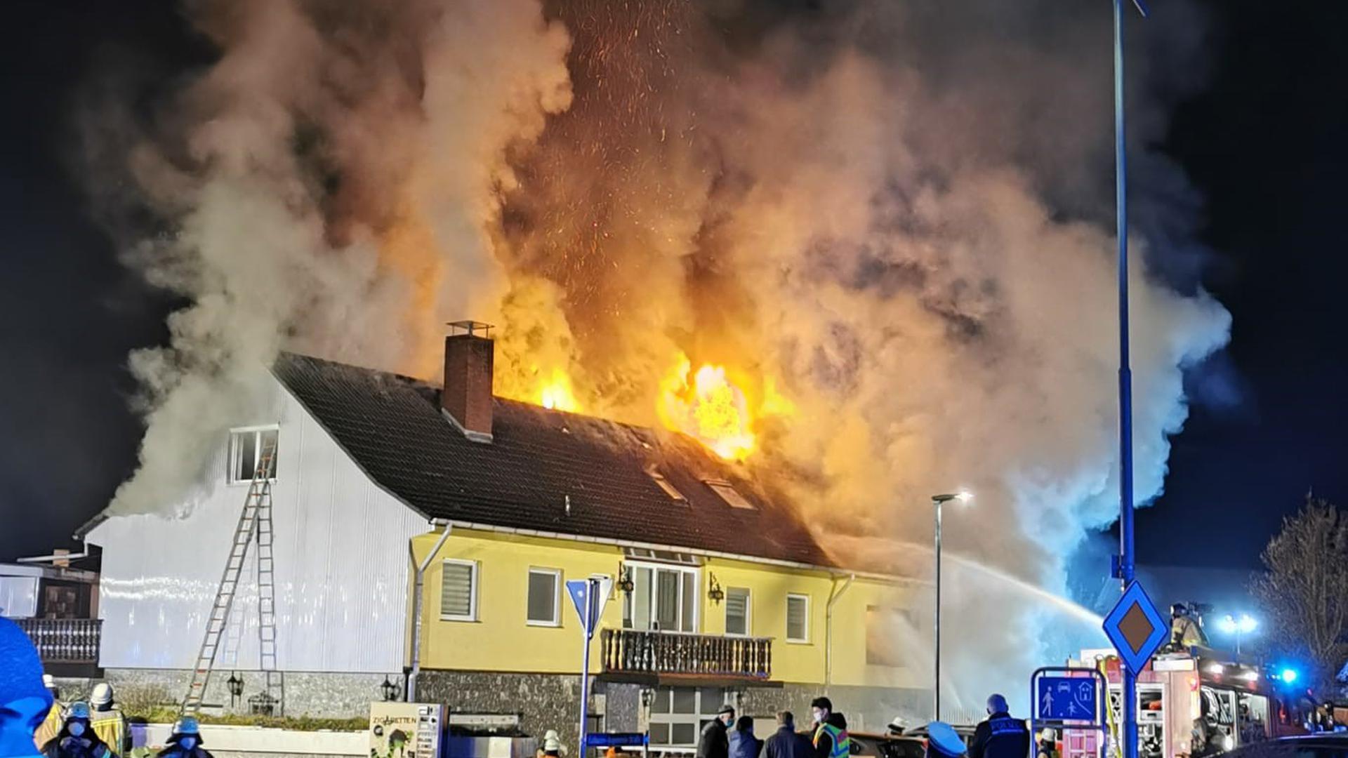 Flammen lodern aus einem Haus. Davor Schaulustige und Einsatzkräfte.