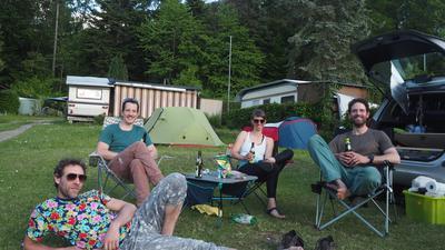 Vier Menschen sitzen auf einem Campingplatz