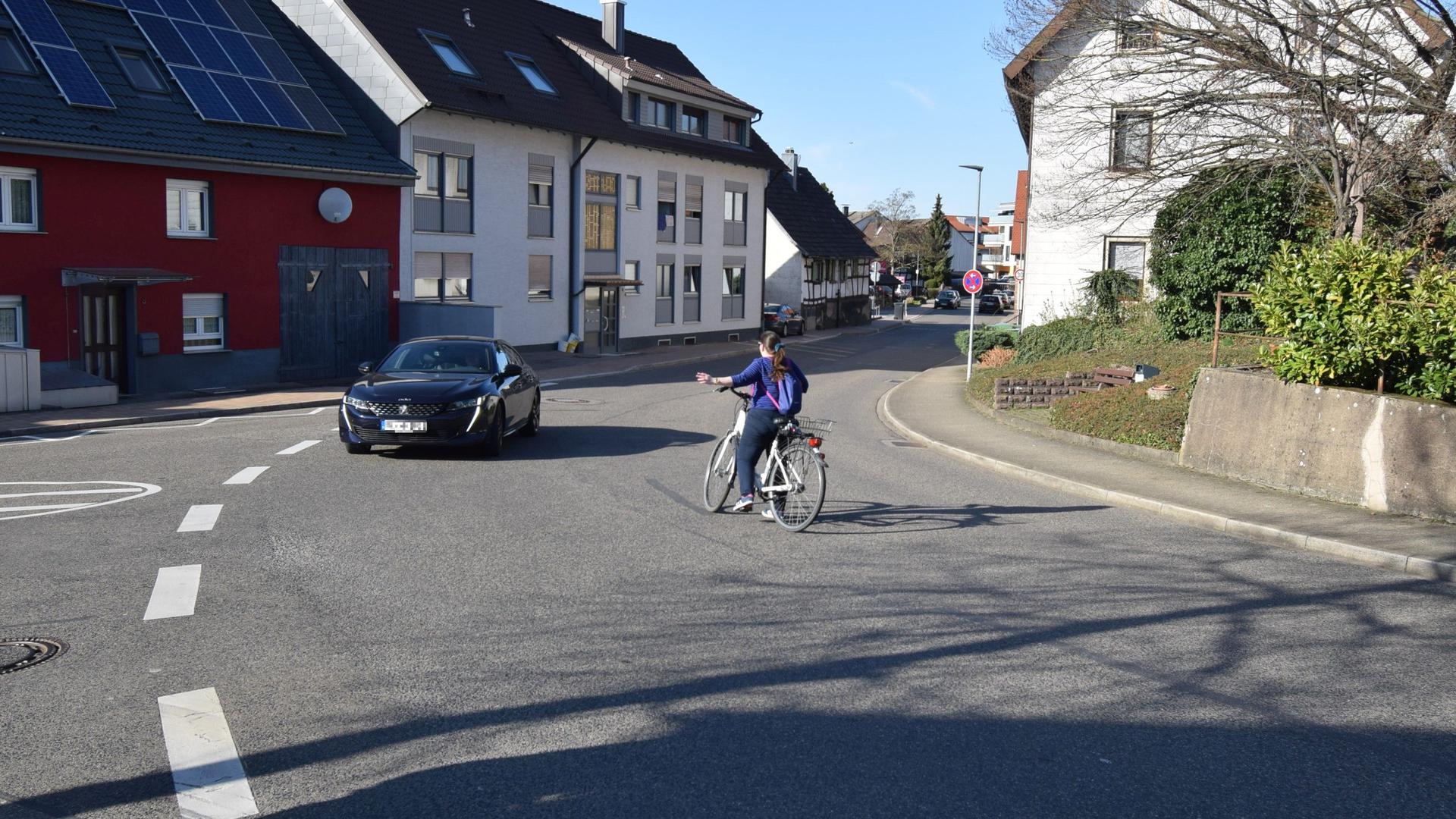 Eine Radfahrerin will von der Richard-Wagner-Straße in Malsch nach links in die Neudorfstraße einbiegen. Sie wartet in der Mitte der Fahrbahn, bis ein Auto im Gegenverkehr vorbeigefahren ist.