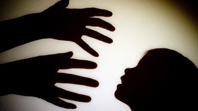 ILLUSTRATION -Schatten von Händen einer erwachsenen Person und dem Kopf eines Kindes an einer Wand eines Zimmers. Jugendmediziner haben einen besseren Schutz für Kinder vor Gewalt und eine stärkere Lobby für die Kleinsten gefordert. Tagtäglich würden Jungen und Mädchen Opfer von Vernachlässigung, Missbrauch und Misshandlung, sagte Tanja Brüning, Leiterin der Medizinischen Kinderschutzambulanz an der Vestischen Kinder- und Jugendklinik Datteln der dpa am Rande einer Expertenveranstaltung in Lünen. +++ dpa-Bildfunk +++