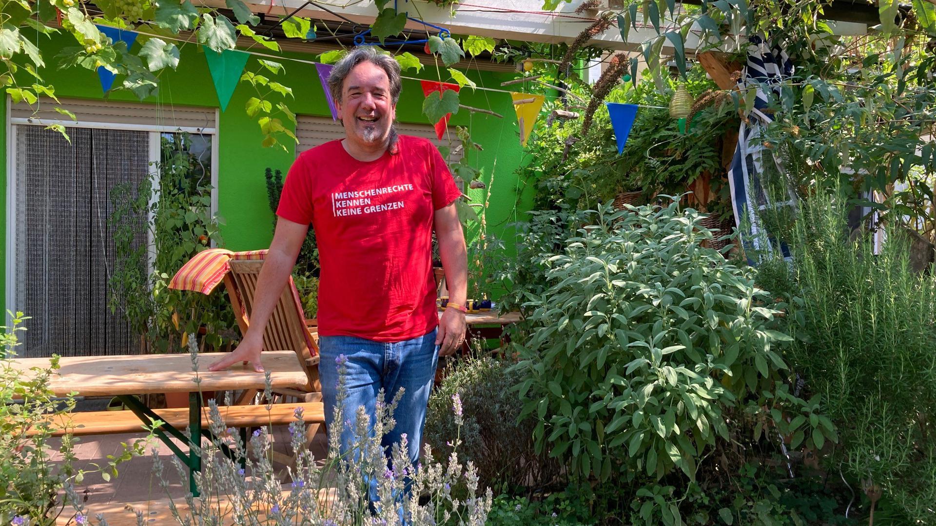 Mann im Garten vor grünem Haus
