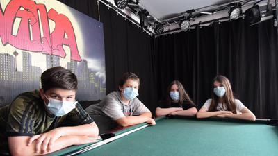Vier Jugendliche lehnen auf einem Billardtisch