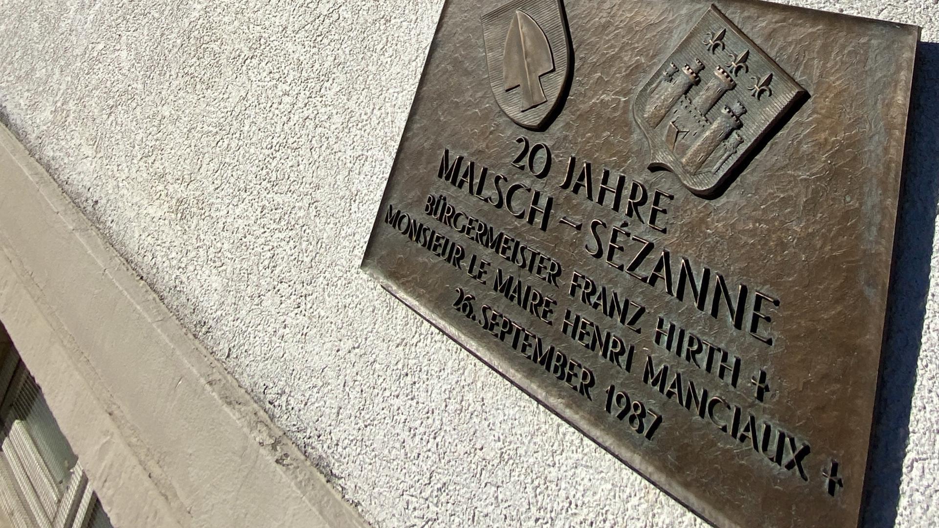 Tafel auf dem Malscher Rathaus bei Sonnenschein.