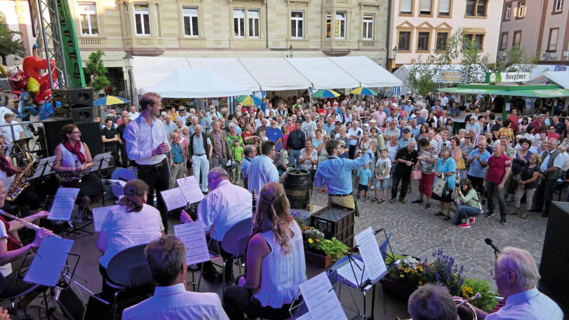 Den Fassanstich zu Klängen des Musikvereins Ettlingen übernahm Bürgermeister Moritz Heidecker (Mitte mit Bierkrug), sodann floss kräftig Freibier.