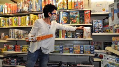 Frau greift in ein Regal mit Spielen