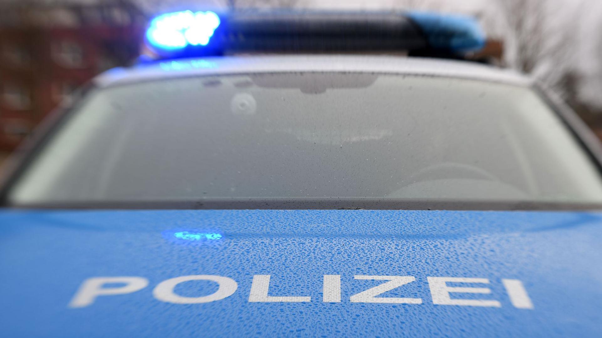 Ein Streifenwagen der Polizei steht mit eingeschaltetem Blaulicht.