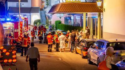 Feuerwehrleute und Hotelgäste stehen vor dem Eingang des Hotels in Ettlingen.