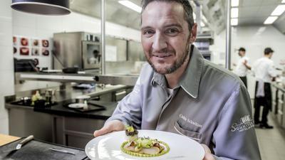 """Cédric Schwitzer steht in seiner Küche im """"Schwitzer's"""" in Waldbronn und hält einen Teller in die Kamera."""