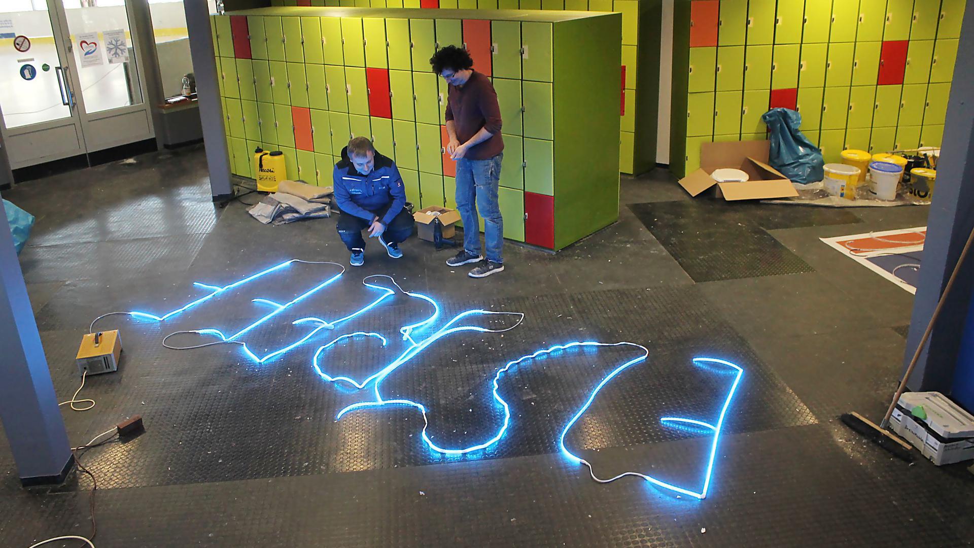 Das LED-Eistrefflogo muss erst außerhalb vom Eis getestet werden. Alexander Schroth und Michael Müller (von links) nehmen es in Augenschein.