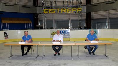 Drei Männer sitzen an Tischen auf einer Eisfläche. Sie unterschreiben jeweils einen Vertrag.