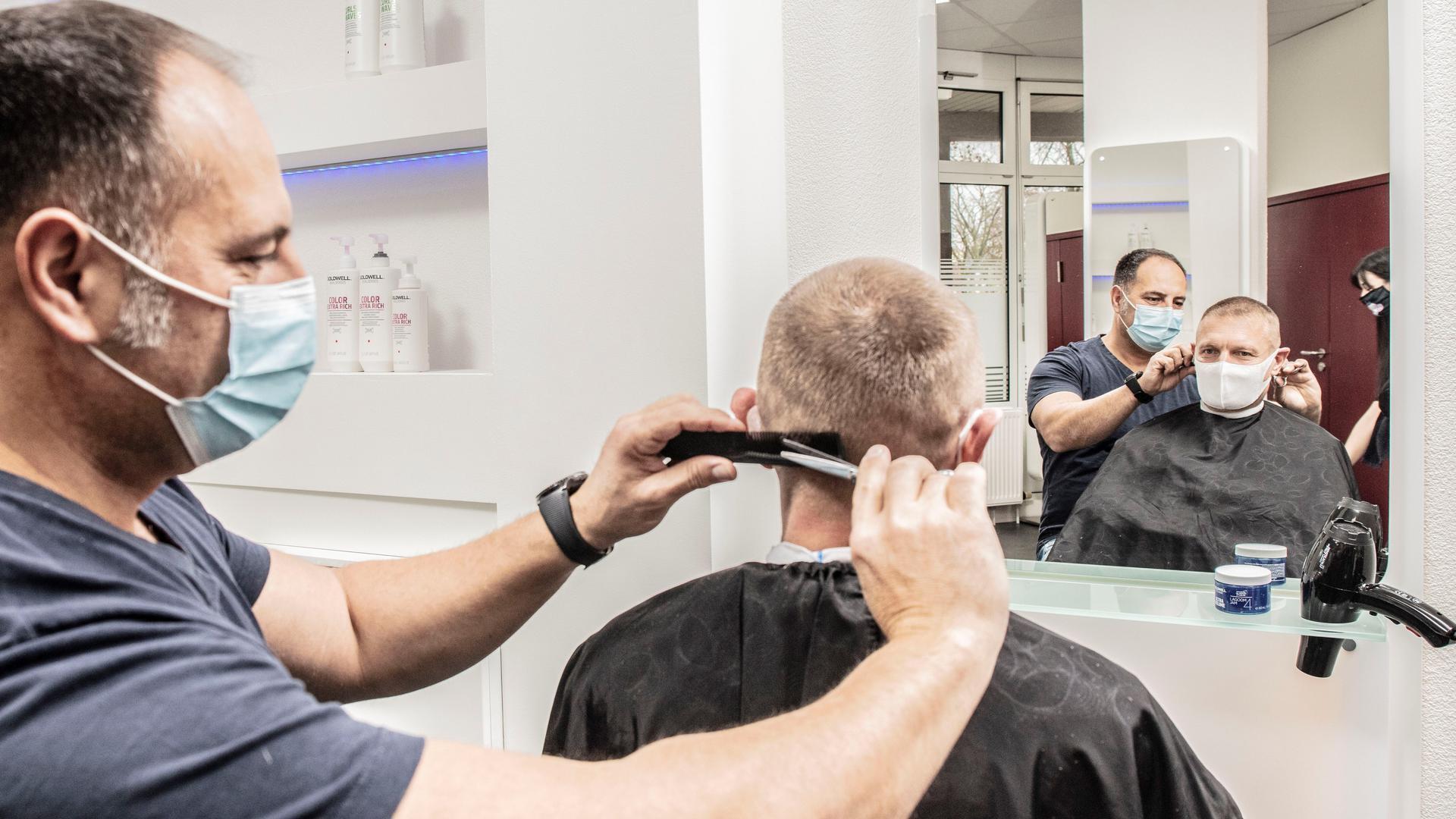 Friseur schneidet einem Mann die Haare.
