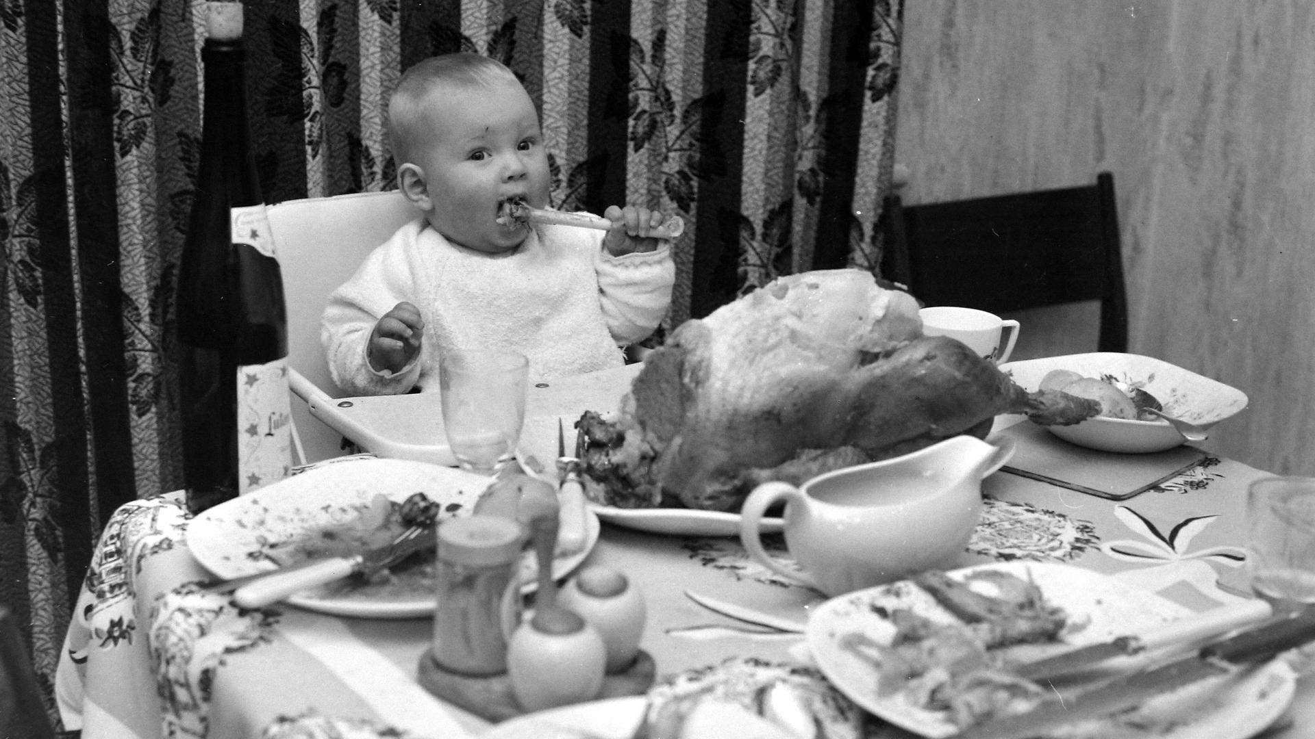 CHILDREN EGGITT TIMOTHY FIRST CHRISTMAS SUCKING TURKEY BONE ; 27 DECEMBER 1964, Copyright: Topfoto PUBLICATIONxINxGERxSUIxAUTxONLY UnitedArchivesIPU490666
