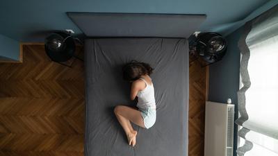 Eine Frau liegt mit angewinkelten Beinen seitlich auf einem Bett.