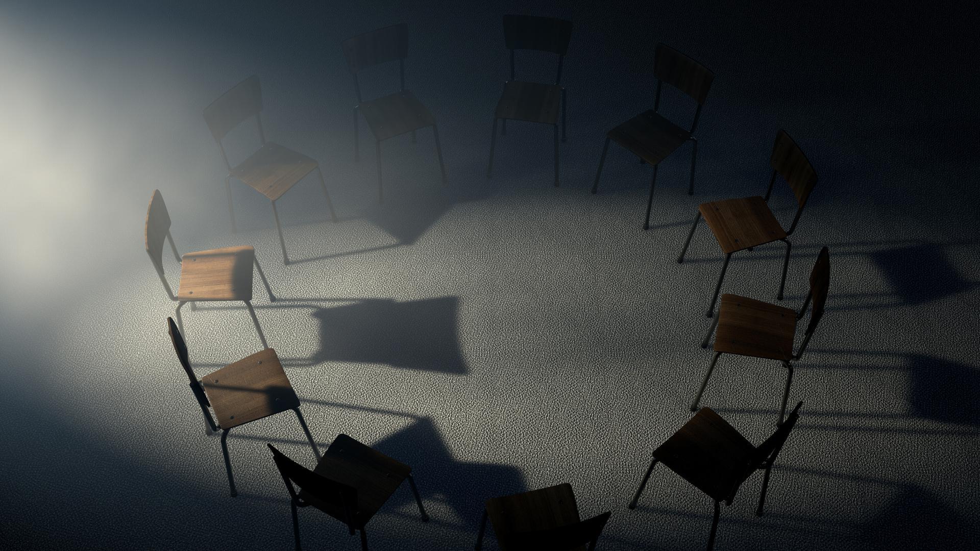 Stühle stehen in einem Kreis in einem dunklen Raum.