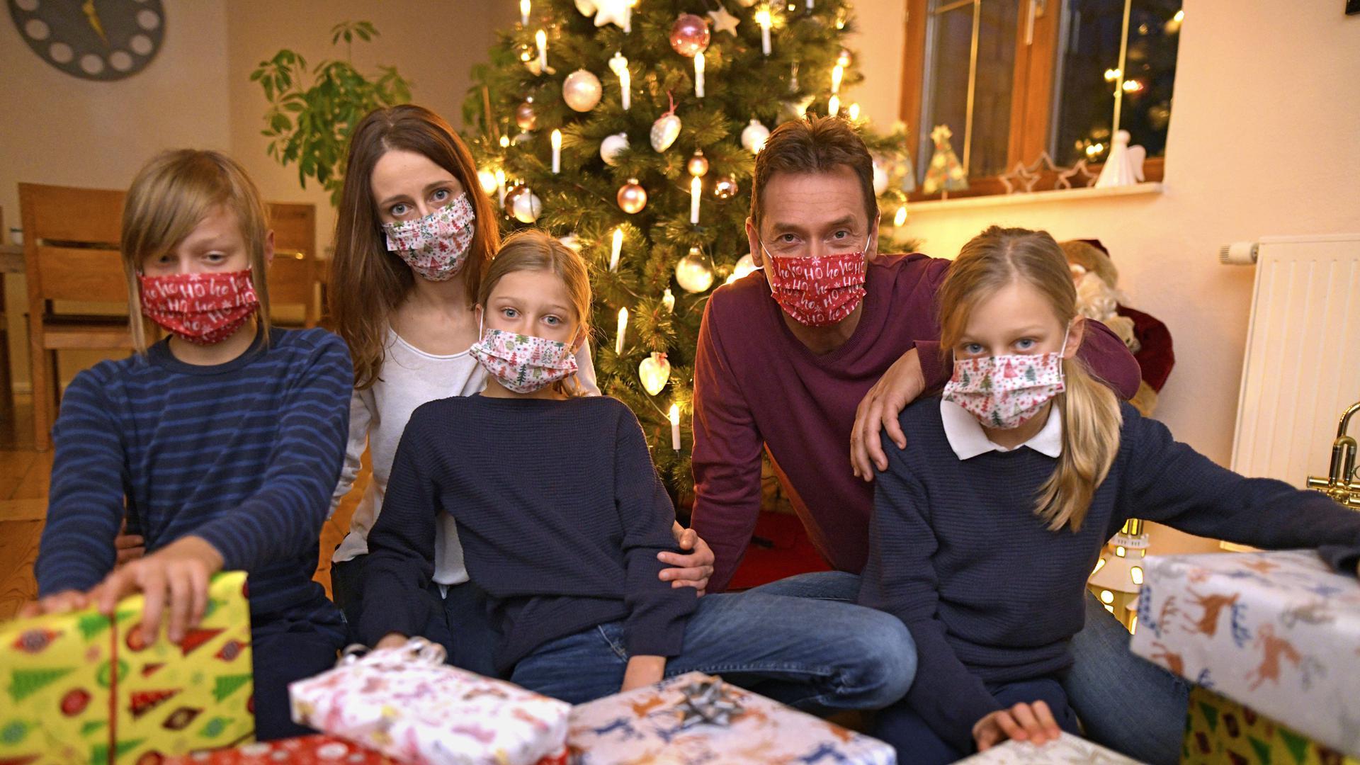 Eine Familie im Allgäu sitzt mit Mund-Nasenschutz-Masken am Heiligen Abend vor dem Weihnachtsbaum im Wohnzimmer, Kontaktverbote und Ausgangsbeschränkungen machen der Bevölkerung zur Corona-Zeit das Leben schwer, die gewohnten Treffen unter den Familien sind dieses Jahr wegen der Pandemiebeschränkungen nur eingeschränkt möglich.