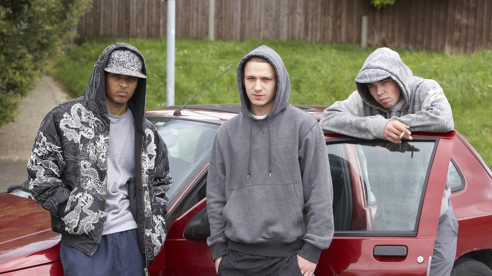 Drei junge Männer stehen rund um ein rotes Auto. Sie tragen Kapuzenpullis und Schirmmützen.