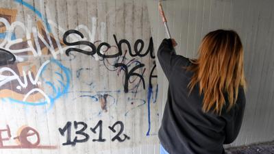 Eine Jugendliche beseitigt in einer Unterführung in Graffitis.