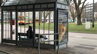 Ein wohnungsloser Mann sitzt seit Wochen an einer Bushaltestelle am Mühlburger Tor.
