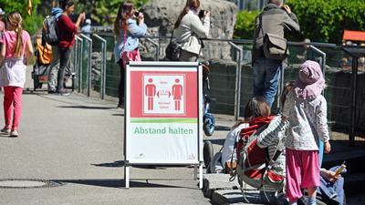 Besucher des Karlsruher Zoos stehen an einem Gehege. Der Zoo muss wegen der Corona-Krise wieder schließen.