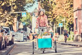 Eine Frau fährt mit einem Lastenrad durch eine Straße. Sie transportiert damit ihren Wocheneinkauf mit Obst und Gemüse.